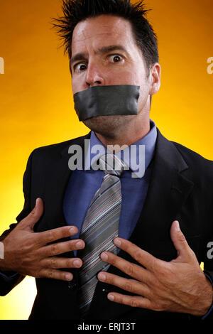 L'homme d'affaires contre fond jaune porte le ruban adhésif sur sa bouche Banque D'Images