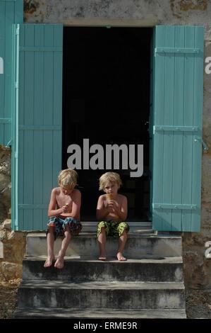 Deux garçons assis à l'extérieur d'une porte avec obturateur en France profiter du soleil à la fois manger une glace Banque D'Images