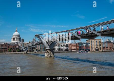 Les gens de marcher à travers Millenium Bridge sur la Tamise, avec Saint Pauls cathédrale en arrière-plan, London, Banque D'Images