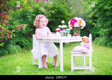 Adorable bébé fille pour son anniversaire jouer tea party avec ours en peluche poupée jouet, plats, cup cakes et muffins dans le jardin ensoleillé
