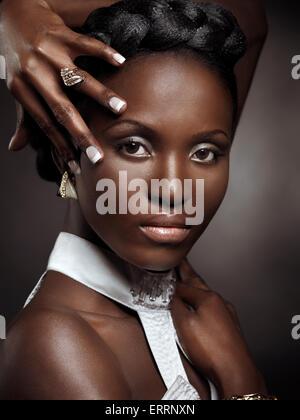 Belle jeune femme afro-américaine de beauté artistique portrait isolé sur fond noir Banque D'Images