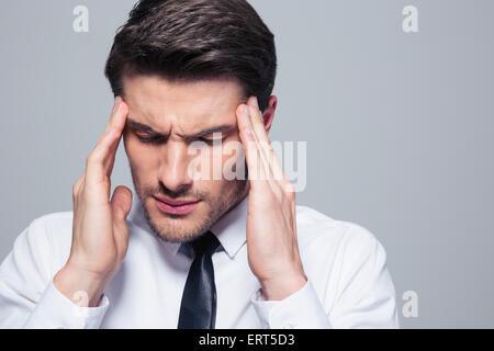 Businessman having maux sur fond gris Banque D'Images