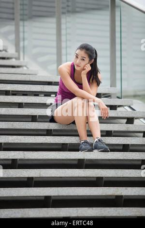 Jeune femme se reposant sur l'escalier après l'exercice Banque D'Images