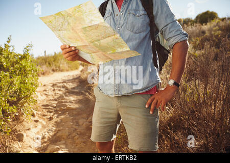 Cropped shot of young man hiking in countryside lire une carte routière pour les directions.