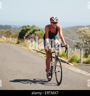 Cycliste femme athlète de triathlon en descente sur route de campagne. Young woman riding bicycle sur route ouverte, Banque D'Images