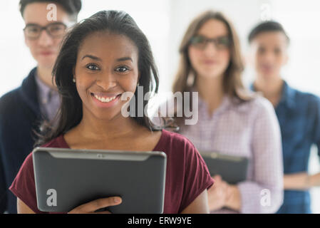 Close up of smiling businesswoman holding digital tablet in office Banque D'Images