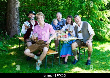 Famille bavaroise assis dehors sur un banc et boire de la bière Banque D'Images