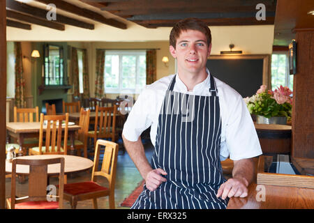 Les blancs et un tablier Chef portant Sitting in Restaurant Banque D'Images
