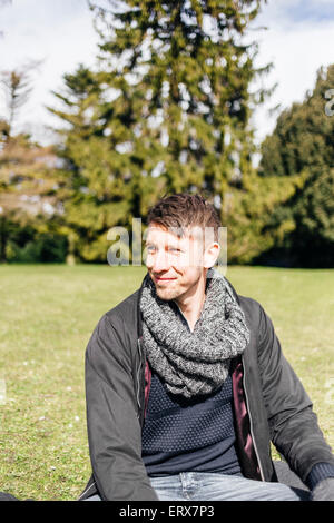Young man sitting in park Banque D'Images