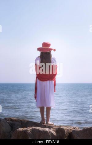 Une jeune fille en robe blanche avec chapeau rouge et châle est debout sur les rochers au bord de la mer Banque D'Images