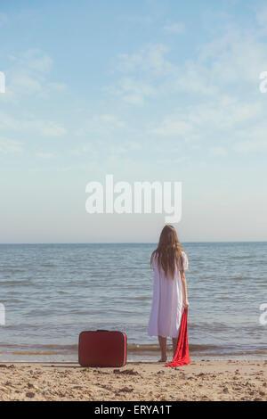 Une jeune fille en robe blanche est debout sur une plage avec une écharpe rouge et laissé une valise rouge derrière Banque D'Images
