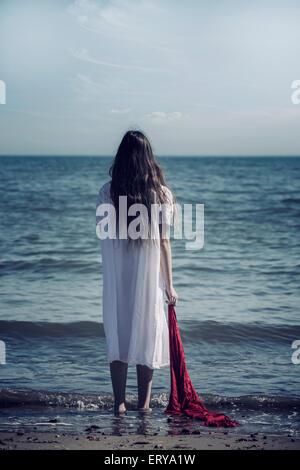 Une jeune fille en robe blanche est debout sur une plage avec une écharpe rouge Banque D'Images
