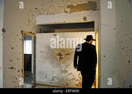 Juif orthodoxe inspecte les murs endommagés dans la région de grenade et de balles à nariman house; Bombay Mumbai Banque D'Images