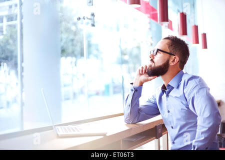 Pensive businessman at laptop in cafe Banque D'Images