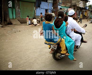 Une famille de cinq membres à cheval sur une moto dans la ville du textile de Malegaon Maharashtra; Inde; Banque D'Images