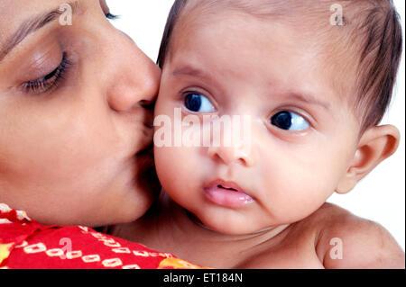 Indian Mère embrassant bébé enfant joues fond blanc - M.#736k&la rmm - 179691 Banque D'Images