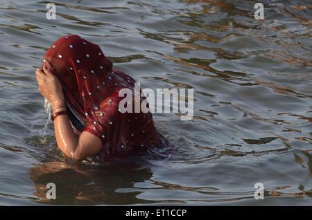 Femme se baignant dans la rivière du Gange à Varanasi Ghat Uttar Pradesh Inde Banque D'Images
