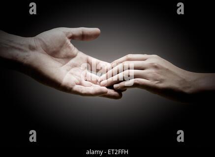 Deux mains se touchent sur fond noir, notion de solidarité ou de l'empathie. Banque D'Images
