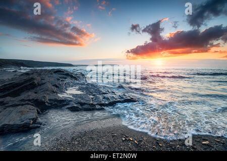 Ciel coucher de soleil spectaculaire sur la plage de la baie Trevone Padstow à Cornwall Banque D'Images