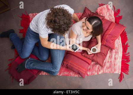 Mid adult man en utilisant un téléphone mobile et sa femme de boire du café à côté de lui, Munich, Bavière, Allemagne