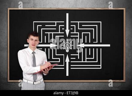 Businessman with clipboard et de dessin sur chalk board maze