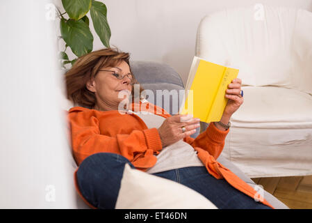 Senior woman reading a book while lying on sofa at home, Munich, Bavière, Allemagne Banque D'Images