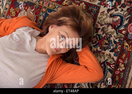 Portrait of senior woman lying on floor, Munich, Bavière, Allemagne