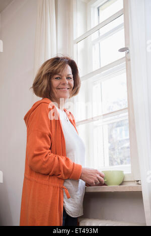 Portrait of senior woman smiling avec avoir une tasse de thé à la maison, Munich, Bavière, Allemagne