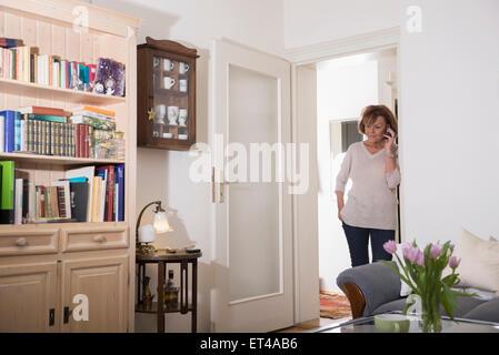 Senior Woman talking on mobile phone à porte, Munich, Bavière, Allemagne