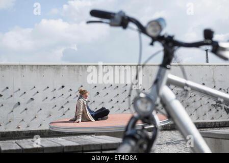 Jeune femme en parc à thème avec en premier plan vélo Allemagne Bavière Munich