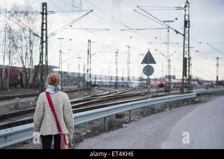 Vue arrière d'une jeune femme curieusement à la gare de chemin de fer sur la Bavière Munich Allemagne