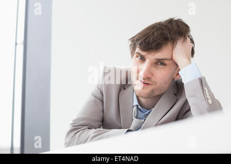 Businessman leaning on desk in office, Leipzig, Saxe, Allemagne