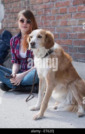 Jeune femme avec chien en face de mur de briques, Munich, Bavière, Allemagne
