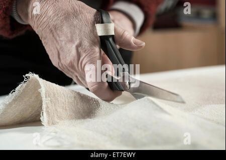 Designer de mode féminine senior tissu coupe avec des ciseaux en atelier Bavaria Allemagne Banque D'Images