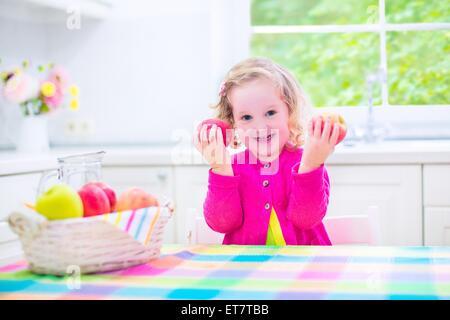 Drôle rire heureux enfant, adorable bébé fille avec des cheveux bouclés portant un chandail rose, manger des pommes Banque D'Images
