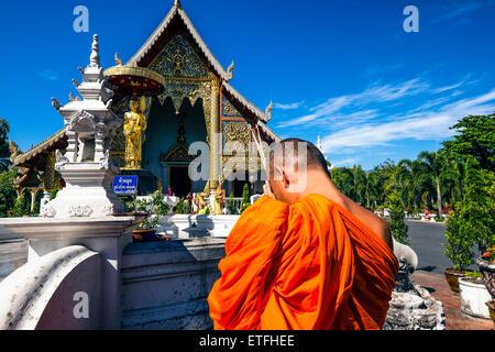 L'Asie. La Thaïlande, Chiang Mai. Wat Phra Singh. Un moine en prière devant la statue en or d'un moine vénéré. Banque D'Images