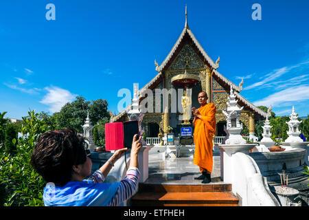 L'Asie. La Thaïlande, Chiang Mai. Wat Phra Singh. Monk se faire photographier devant la statue en or d'un moine Banque D'Images