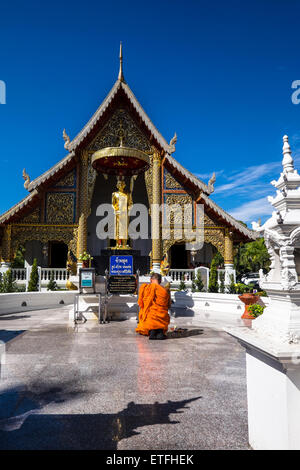 L'Asie. La Thaïlande, Chiang Mai. Wat Phra Singh. Moine à genoux priant devant la statue en or d'un moine vénéré. Banque D'Images