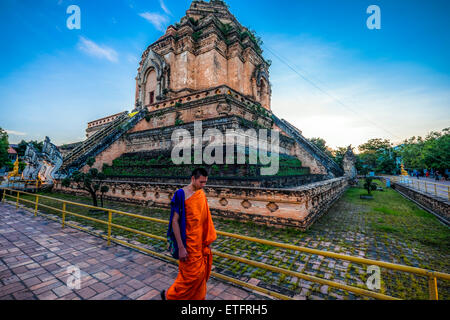 L'Asie. La Thaïlande, Chiang Mai. Wat Phra Singh. Monk walking en face de l'ancien temple. Banque D'Images