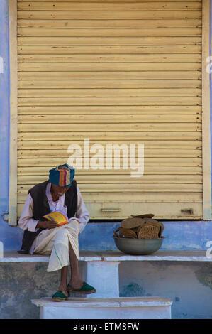 La lecture de l'homme Indien assis à côté de bol de bouse de chameau. Pushkar, Rajasthan, India Banque D'Images