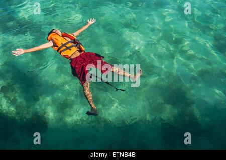 Teenage boy portant un gilet de sauvetage, flottant dans la mer, l'île de Salakan, Semporna, Sabah, Malaisie Banque D'Images
