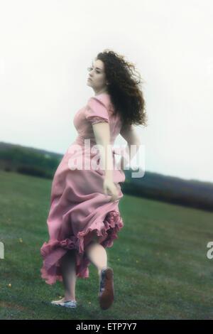 Une femme dans une robe rose est exécuté sur un pré Banque D'Images