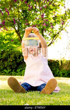 Petite fille assise sur un pré à la recherche à l'insecte peut Banque D'Images