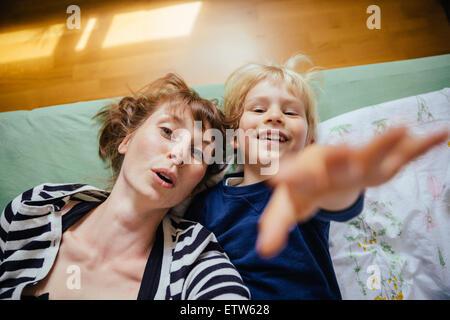 Mère et petit fils lying on bed tendre la main à l'appareil photo Banque D'Images