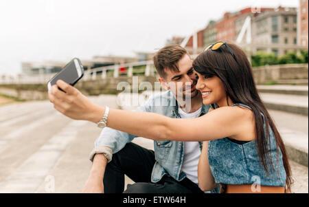 L'Espagne, Gijon, jeune couple amoureux en tenant avec smartphone selfies Banque D'Images