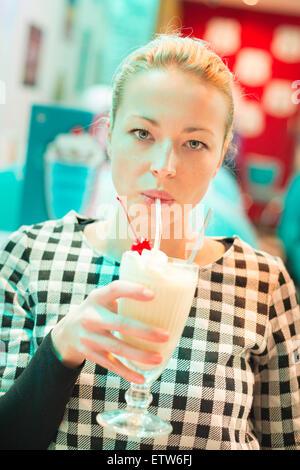 Woman drinking milk shake au diner. Banque D'Images