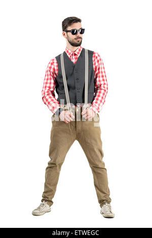 Confiant à bretelles holding hipster de là. La pleine longueur du corps portrait studio isolated over white background. Banque D'Images