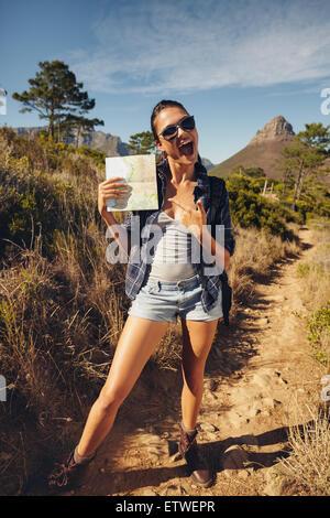 Portrait de jeune femme hiker montrant une carte. Caucasian woman hiking in countryside sur journée d'été. Banque D'Images