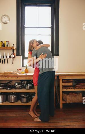 Happy young woman câlins par son petit ami dans la cuisine. Cheerful couple dans la matinée à la maison. Banque D'Images