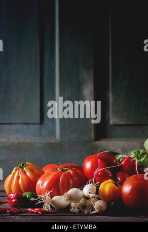 Tas de légumes colorés frais mûrs tomates, piments, l'oignon vert et bande de radis plus vieille table en bois. Banque D'Images